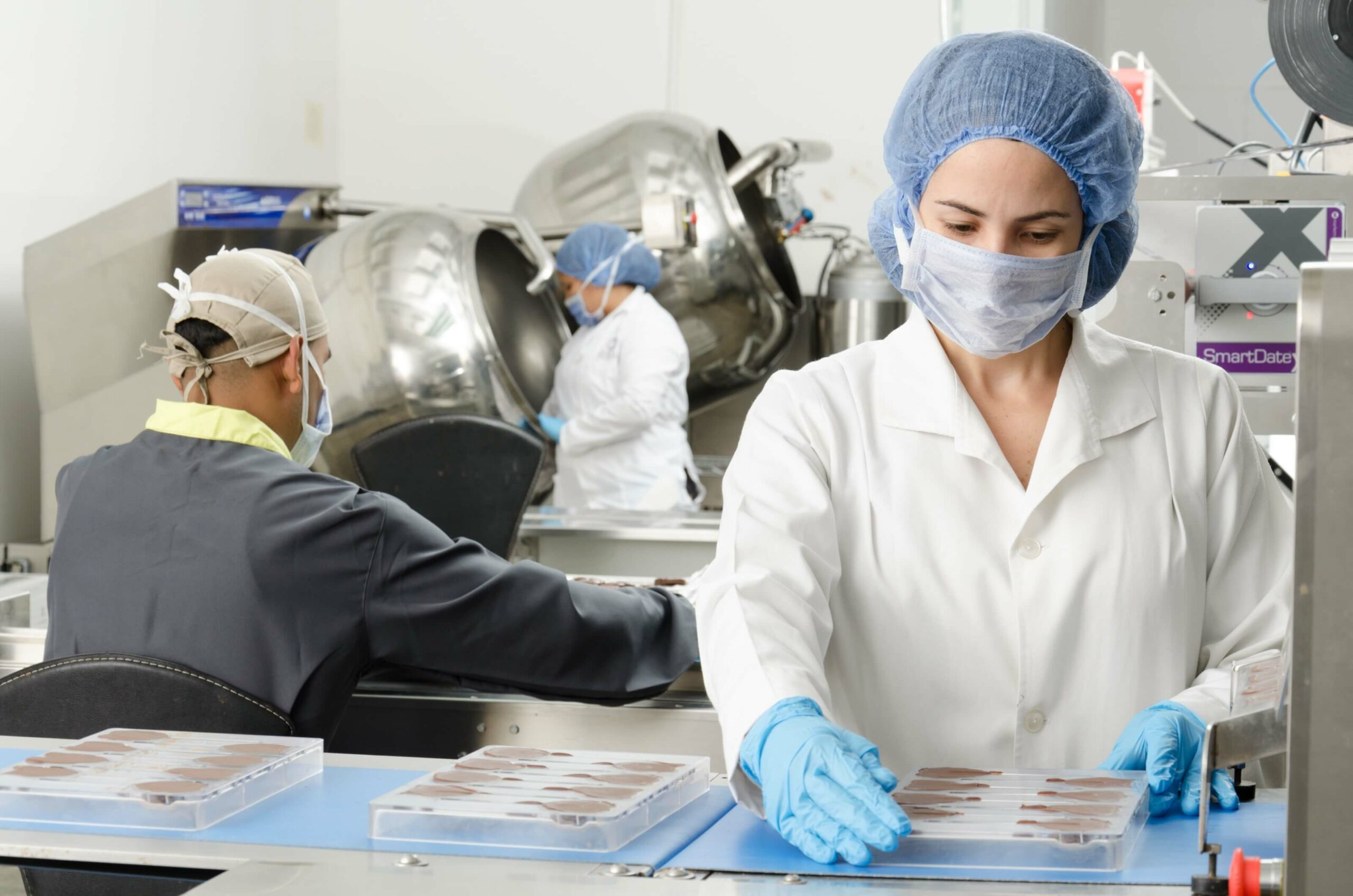 personnel wearing protective suits inside a lab